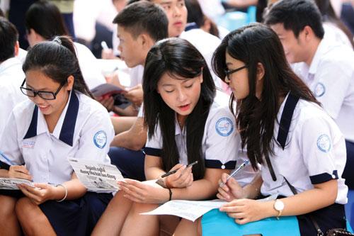 Học sinh Trường THPT Marie Curie (TP.HCM) trao đổi khi thực hiện phiếu trắc nghiệm ngành nghề trong buổi khai mạc chương trình Tư vấn mùa thi 2013 - Ảnh: Đào Ngọc Thạch
